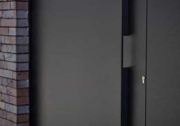 דלת כניסה במישור הקיר, עם ידית ייחודית